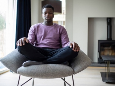 Close Up Of Peaceful Teenage Boy Meditating Sitting In Chair At Home